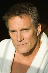 Portrait of a mature man with blue eyes wearing a white bathrobe