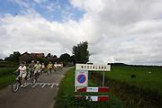Een groep fietsers rijdt het Overijsselse gehucht Nederland uit<br /> <br /> Cyclists in the Dutch town Nederland