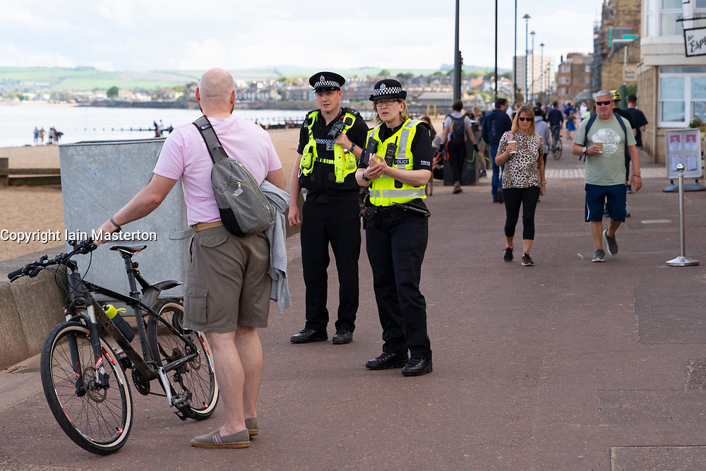 Portobello, Scotland, UK. 9 May 2020. Images from holiday weekend Saturday afternoon during Covid-19 lockdown on promenade at Portobello. Promenade and beach were relatively quiet with a low key police presence. Pictured;  Police speak with angry man who was asked to leave with his group of friends. Iain Masterton/Alamy Live News