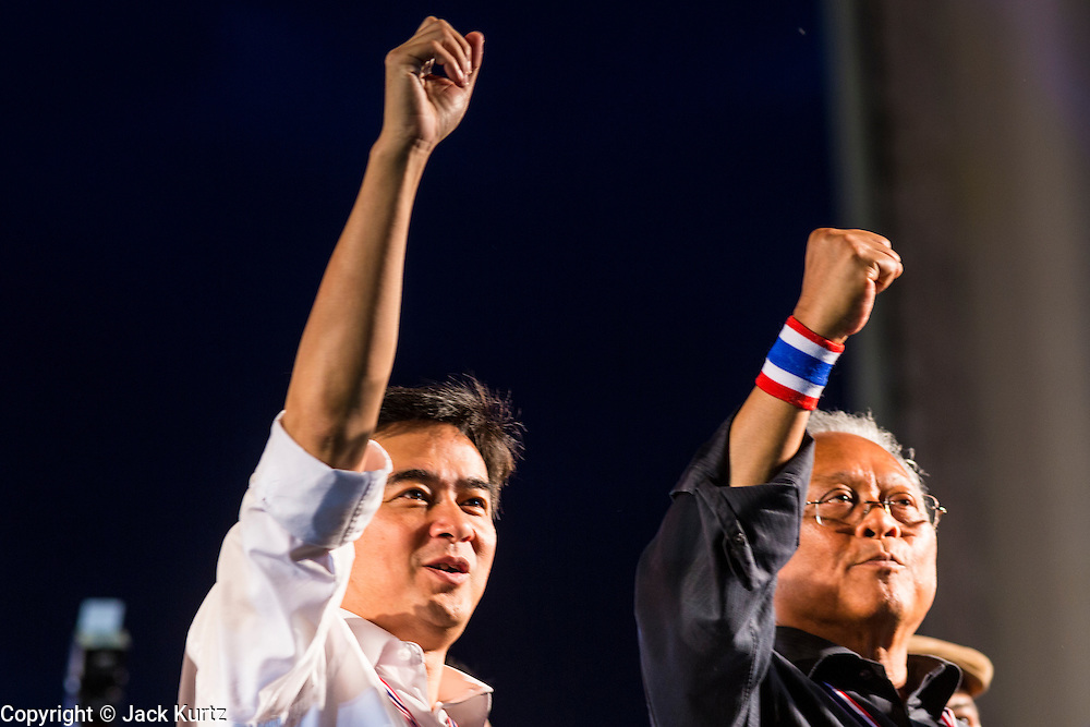 """15 NOVEMBER 2013 - BANGKOK, THAILAND:  Former Thai Prime Minister ABHISIT VEJJAJIVA and SUTHEP THAUGSUBAN, leader of anti-government protests and the former Deputy Prime Minister of Thailand, stand on the stage at Democracy Monument during an anti-government protest in Bangkok. Tens of thousands of Thais packed the area around Democracy Monument in the old part of Bangkok Friday night to protest against efforts by the ruling Pheu Thai party to pass an amnesty bill that could lead to the return of former Prime Minister Thaksin Shinawatra. Suthep announced an all-out drive to eradicate the """"Thaksin regime."""" The protest Friday was the biggest since the amnesty bill issue percolated back into the public consciousness. The anti-government protesters have vowed to continue their protests even though the Thai Senate voted down the bill, thus killing it for at least six months.    PHOTO BY JACK KURTZ"""