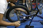 Israel, Tel Aviv, Bicycle shop. Man fixes a bike