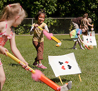 Kindergarteners Ashley Herrera and Nicole Johnson enjoy a game of Flamingo Croquet during the Alice in Wonderland themed Field Day events at Elm Street School Tuesday morning.   (Karen Bobotas/for the Laconia Daily Sun)
