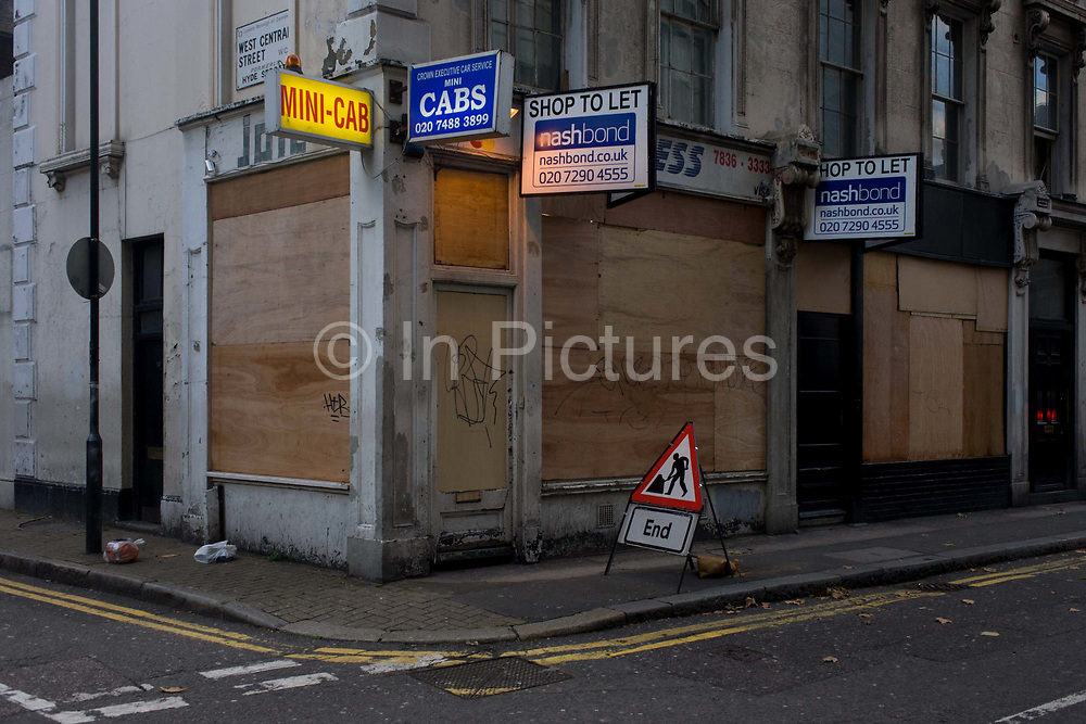 A boarded up central London mini cab business and an End of works triangle sign on a Holborn corner. The visual pun plays off the triangular sign that tells us that work has ended, a message we also understand from the plyboard attached to the former business premises, securing it from vandals, squatters or illegal occupation. A security light burns 24/7 and the old cab office's details along with the property agent's.
