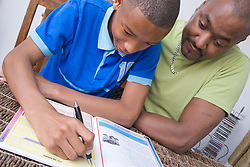 Father helping his teenaged son with his homework,