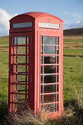 Old red telephone box on Orkney; Scotland,