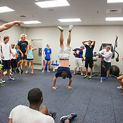 SwimMAC Director Of Coaching and coach of the SwimMAC Elite team does a handstand during a workout.