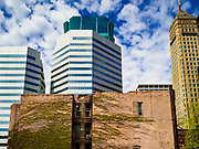 03 MAY 2017 - MINNEAPOLIS, MN: A condemned apartment building in downtown Minneapolis with the city skyline behind it. The skyways are enclosed pedestrian overpasses that connect downtown buildings. The Minneapolis Skyway was started in the early 1960s as a response to covered shopping malls in the suburbs that were drawing shoppers out of the downtown area. The system grew sporadically until 1974, when the construction of the IDS Center and its center atrium, called the Crystal Court, served as a hub for the downtown skyway system. There are 8 miles of skyways, connecting most of the downtown buildings from Target Field (home of the Minnesota Twins) to US Bank Stadium (home of the Minnesota Vikings). In the last five years many upscale downtown apartment buildings and condominium developments have been added to the system, allowing downtown residents to live and work downtown without going outside.    PHOTO BY JACK KURTZ