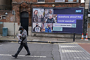 A south Londoner wearing a face covering walks past a governement NHS (national Health Service) billboard giving a link for official information relating to Covid vaccine facts, an attempt to counter misinformation and conspiracy theories to the public in Lambeth - a borough that has seen high infection rates of Covid and Delta variants, on 6th July 2021, in Camberwell, London, England.