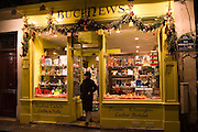 Woman leaves a Parisian newsagents shop in Rue Gregoire de Tours, Paris, France