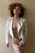 Portrait of sexy nude woman leaning against wall in apartment wearing a white jacket