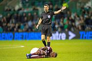 Referee Kevin Clancy gives a foul, as Arnaud Djoum (#10) of Heart of Midlothian lies injured during the Ladbrokes Scottish Premiership match between Hibernian FC and Heart of Midlothian FC at Easter Road Stadium, Edinburgh, Scotland on 29 December 2018.