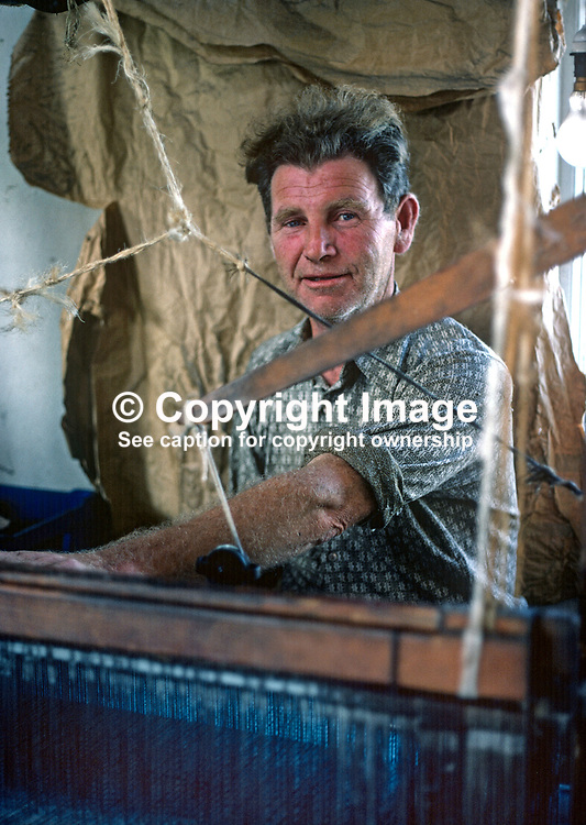 Home weaver and his loom, Ardara, Co Donegal, Rep of Ireland. 197809000246c.<br /> <br /> Copyright Image from Victor Patterson, Belfast, UK<br /> <br /> t: +44 28 9066 1296 (from Rep of Ireland 048 9066 1296)<br /> m: +44 7802 353836<br /> e: victorpattersonbelfast@gmail.com<br /> <br /> www.images4media.com<br /> <br /> Please see my full Terms and Conditions of Use at https://www.images4media.com/p/terms-conditions - it is IMPORTANT that you familiarise yourself with them.<br /> <br /> Images used online incur an additional cost. This cost should be agreed in writing in advance. Online images must be visibly watermarked i.e. © Victor Patterson or that of the named photographer within the body of the image. The original metadata must not be deleted from images used online.<br /> <br /> This image is only available for the use of the download recipient i.e. television station, newspaper, magazine, book publisher, etc, and must not be passed on to a third party. It is also downloaded on condition that each and every usage is notified within 7 days to victorpattersonbelfast@gmail.com.<br /> <br /> The right of Victor Patterson (or the named photographer) to be identified as the author is asserted in accordance with The Copyright Designs And Patents Act (1988). All moral rights are asserted.