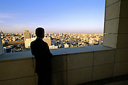 A businessman looks out over cityscape in late evening from high on the balcony of a nearby hotel - Amman, Jordan.