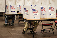 Voters take their time reading over theballots at Belmont High School on Tuesday morning.  (Karen Bobotas/for the Laconia Daily Sun)