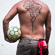 "Leandro ""Maradona"" Marques, an ardent Flamango FC fanatic with a rosary and crucifix in the shape of the Brazilian territorial boundaries , with Flamengo's anthem tattooed onto his back. As he says"" every time his team make a goal he cries with joy, his girlfriends come second in importance to Flamengo FC."