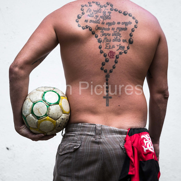 """Leandro """"Maradona"""" Marques, an ardent Flamango FC fanatic with a rosary and crucifix in the shape of the Brazilian territorial boundaries , with Flamengo's anthem tattooed onto his back. As he says"""" every time his team make a goal he cries with joy, his girlfriends come second in importance to Flamengo FC."""