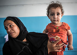 "© Licensed to London News Pictures. 19/07/2014. Gaza.   ""When I hold my daughter in my arms I forget the whole world.""  Comments Ablu Abu Hamillah (38) as she joins over 600 in a UN School within Gaza city.   Many residents were forced to flee as the war in Gaza killed over over 2,200 people - most of them Palestinians - and many more injured, during 50 days of violence. A ceasefire was agreed between Israel and Hamas on 26 August.      Photo credit : Alison Baskerville/LNP"