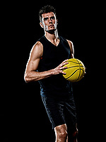 one caucasian young basketball player man in studio isolated on black background