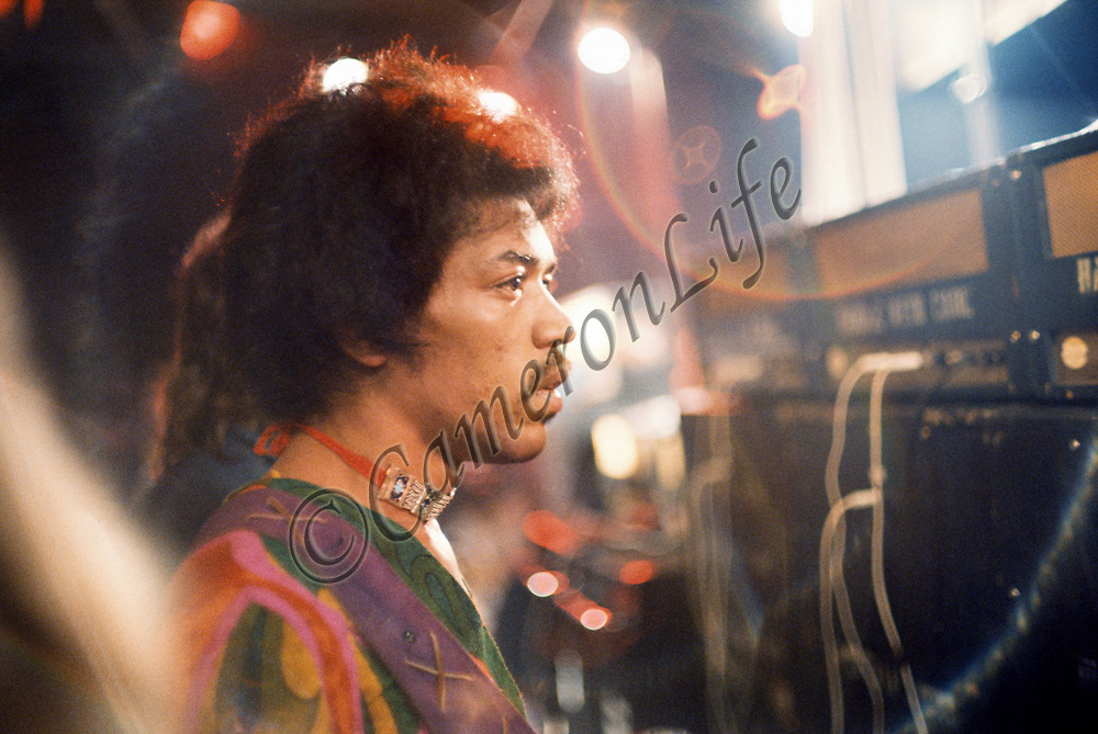 Jimi Hendrix - in pensive. mood .- Born Johnny Allen Hendrix on November 27th 1942, Jimi is shown here looking out over the vast Isle of Wight festival crowd from off stage - most likely taking a short breather from his exhausting set. Jimi is considered by many to be the greatest electric guitarist in the history of rock music, and one of the most important and influential musicians of his era