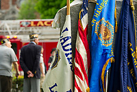 Flags resting against a granite memorial in Veteran's Square as the Memorial Day parade goes by in downtown Laconia.  (Karen Bobotas/for the Laconia Daily Sun)