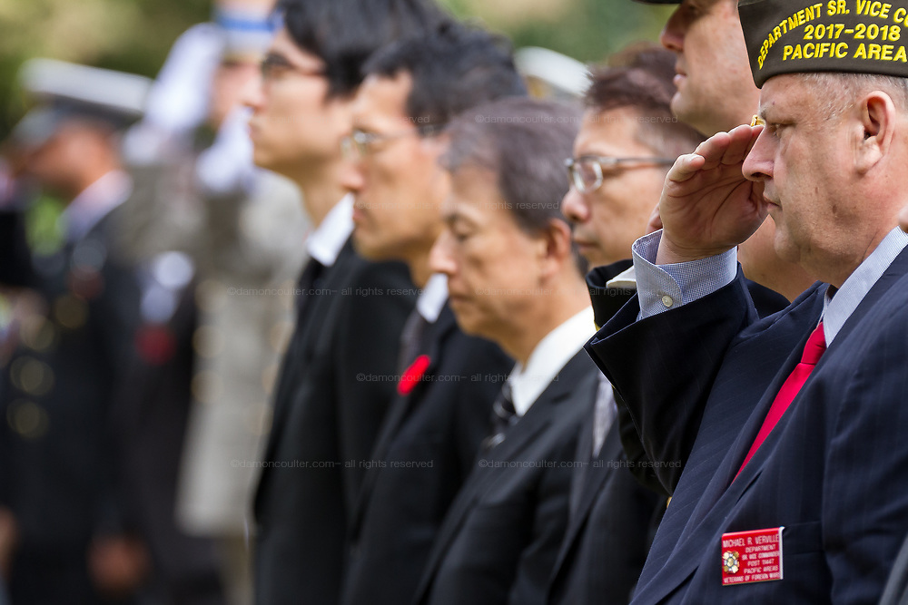 An American military veteran salutes during the Remembrance Sunday ceremony at the Hodogaya, Commonwealth War Graves Cemetery in Hodogaya, Yokohama, Kanagawa, Japan. Sunday November 12th 2017. The Hodagaya Cemetery holds the remains of more than 1500 servicemen and women, from the Commonwealth but also from Holland and the United States, who died as prisoners of war or during the Allied occupation of Japan. Each year officials from the British and Commonwealth embassies, the British Legion and the British Chamber of Commerce honour the dead at a ceremony in this beautiful cemetery.