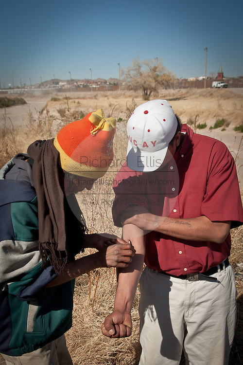 WARNING GRAPHIC CONTENT: Heroin addicts shoot up along the dry riverbed of the Rio Grande River in Juarez, Mexico January 16, 2009 as the US border is seen in the background. An ongoing drug war between cartels for control of the drug routes into the US killed 1600 people in Juarez last year and already 40 since the start of the new year making the city the most violent in Mexico.   (Photo by Richard Ellis)