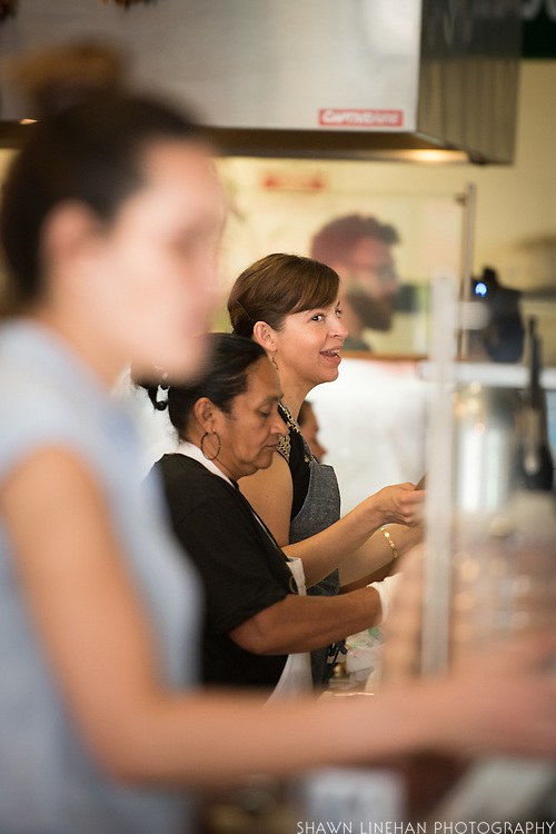 Dominica Rice, owner and chef at Cosecha Cafe in Oakland, California talks with guests as they wait in line to order food.