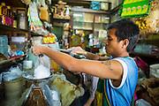 22 JANUARY 2013 - BANGKOK, THAILAND:  A shopkeeper on Chareon Krung Road, in Bangkok's Chinatown, puts out baking supplies.       PHOTO BY JACK KURTZ