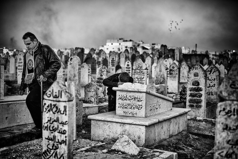 A child prays at the grave of his grandmother.