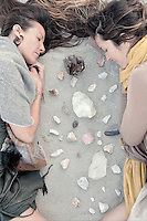 Wild Woman friendship energizing together with crystals in desert wilderness nature. Contemplative women meditating on the earth with healing stone crystals
