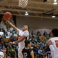 Gallup Bengal Joaquin Ortega (30) drives to the basket for a layup as Miyamura Patriot Lance Evans (12) defends Wednesday night at Gallup High School in Gallup. Gallup took the win 56-51.