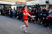 Girl from The Sun race team during the Great Spitalfields Pancake Race on Shrove Tuesday, pancake day, at the Old Truman Brewery, London, UK. This is a fun quirky annual event where competitors come as teams of four people dressed up in costume of some kind. Organised by Alternative Arts raising money for charity.