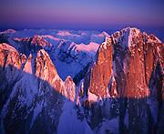 Winter aerial view of granite faces of the Cathedral Spires illuminated at sunset, Kichatna Mountains, Alaska Range, Denali National Park and Preserve, Alaska.