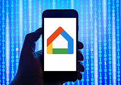 Person holding smart phone with  Google Home  logo displayed on the screen. EDITORIAL USE ONLY