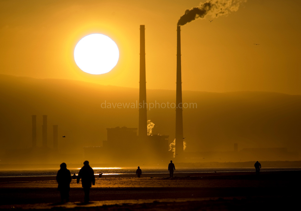 Climate change: Source of solar energy setting behind user of fossil fuel energy - sun setting behind Poolbeg Generating station, Ringsend Dublin, The Walkers are on Bull Island, in North Dublin. Shot at 400mm.