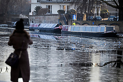 © Licensed to London News Pictures. 31/01/2019. London, UK. A woman takes a picture of frozen water on the canal network in Little Venice, West London, as temperatures in the capital drop to the lowest of the winter so far. Photo credit: Ben Cawthra/LNP