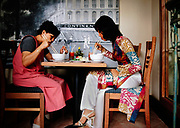 """Vietnamese women dine in the garden of the Hotel Continental in Saigon. A relic of French colonial days, the former Continental Palace caught the imagination of authors like Graham Greene, journalists and spies, who drank and gossiped on its open-sided terrace - """"the Continental Shelf – and made it home during the French and American wars in Vietnam. © Steve Raymer"""