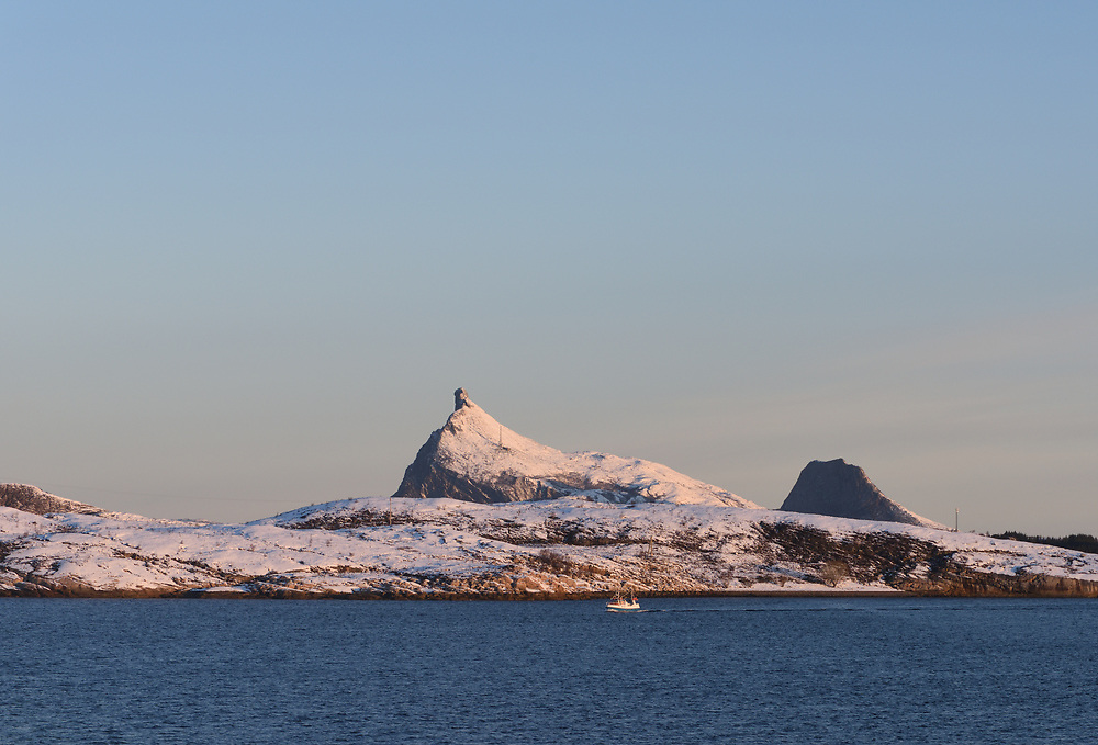 Dramatic hills on the island of Storseløy  seen from the Hurtigruten just south of the Arctic Circle. The dramatic peak is Hestmannen. Storseløy,  Rødøy and Lurøy, Nordland, Norway.