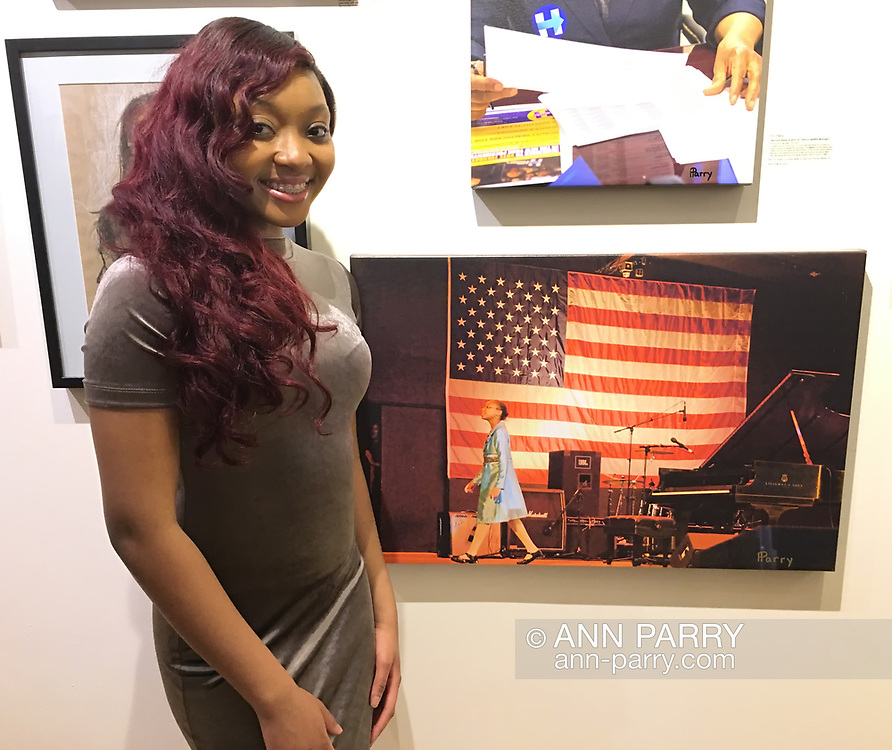 "Huntington, New York, USA. March 5, 2017. Sheimyrah Mighty, 18, next to 2008 photo of herself, at Opening Reception for ""Her Story Through Art"" Invitational Art Show, celebrating Women's History Month, at Huntington Arts Council, Main Street Gallery. Artists Tara Leale Porter, Irene Vitale, Anahi DeCanio, Ann Parry, Show March 2 - 25, 2017."