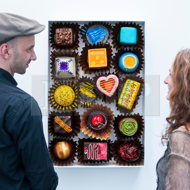"© Licensed to London News Pictures. 19/05/2016. London, UK. Visitors view Peter Anton's ""Lustful Selection"", a mixed media work that looks like a box of delicious chocolates.  Art16 opens at Olympia, in west London.  Now in its fourth edition, the fair brings together over 100 galleries from more than 30 countries showcasing a diverse cross-section of work by contemporary artists from around the world for buyers and art enthusiasts to visit. Photo credit : Stephen Chung/LNP"