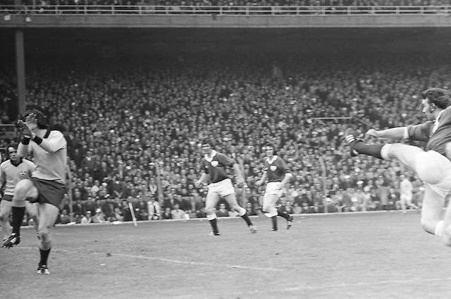 Galway player kicks the ball forcefully as Dublin player blocks his face during the All Ireland Senior Gaelic Football Championship Final Dublin V Galway at Croke Park on the 22nd September 1974. Dublin 0-14 Galway 1-06.