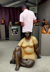 28 April 2013. New Orleans, Louisiana,  USA. .A man sits on a wooden statue at the New Orleans Jazz and Heritage Festival. .Photo; Charlie Varley.