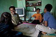Shafiq Syed, 34, is playing with his three children, (left to right) Simran, 7, Nadeem, 4 and Waseem, 11, in his home inside a poor neighbourhood of Bangalore, Karnataka, India. Shaifq has been the main character of the Cannes' Camera D'Or 1988 winner Salaam Bombay, but after the movie he failed to become a star, fell back into poverty and lived on the streets for years before he became a rickshaw (tuk-tuk) driver in his home city of Bangalore, Karnataka State, India.