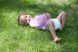 Little girl rolling around in the garden,