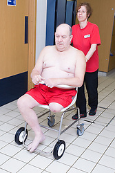 Disabled man; with the assistance of a member of staff; making his way to the swimming pool at his sports leisure centre,