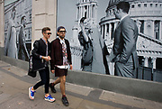 Two men walk past a fashion poster showing a fashion boy and girl and St Paul's Cathedral. The stylish boys walk together along a street in the capital, where the billboards replace the windows of a soon-to-open retail business. The models are the epitome of youth and happiness, with the backdrop of the capital's famous landmark.