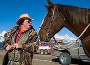 NEWS&GUIDE PHOTO / PRICE CHAMBERS<br /> Ed Coffey talks to his impatient horse Mike as he pulls a treat from its bag Monday morning in Grand Teton National Park. Coffey and Mike work for Tag N' Drag a local game retrieval service.