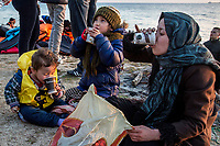 LESVOS, GREECE - FEBRUARY 09: A family take hot drinks given by volunteers after their arrival on a beach in South Lesvos with other refugees and migrants from the Turkish coast on February 09, 2015 in Lesvos, Greece. Photo: © Omar Havana. All Rights Are Reserved