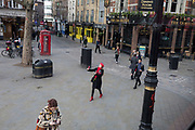A young woman wearing a red theme of beret and scarf, walks down Charing Cross Road at Cambridge Circus in Soho, carrying some Valentine's Day roses, and photographs herself with a beaming smile, on 14th February 2020, in London, England.