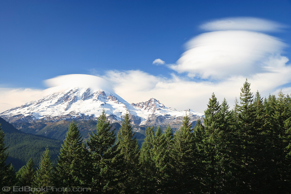 A series of lenticular clouds (Altocumulus standing lenticularis) form and then slip off the summit of Mount Rainier signaling a change to moister weather.  Mount Rainier National Park, WA, USA